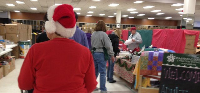 People wait in line to select donated gifts Saturday at the Johnson County Christmas Bureau's Holiday Shop in Olathe.