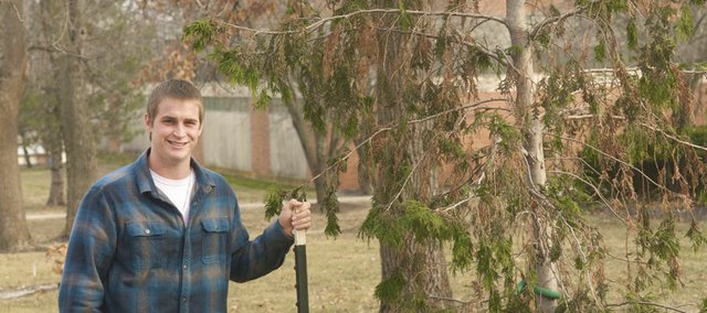 Bryan Kindle stands Monday by a tree on the Baker University campus planted in memory of his teammate, roommate and best friend, Tyler Jeck, who drowned the summer following his freshman year. Kindle will graduate Saturday after an emotional four-and-a-half years on the campus during which he dealt with a life-threatening health issue.