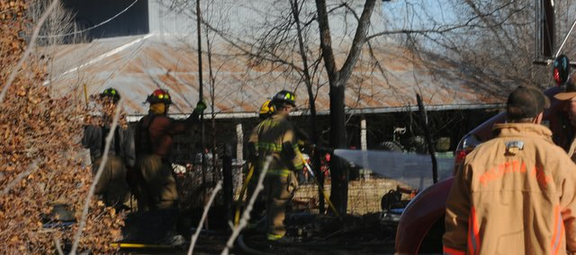 Firefighters spray water Monday morning on the remains of an outbuilding at 1288 N. 400 Rd. The fire at the home of Walt Babbit caused an estimated $10,000 in damages.