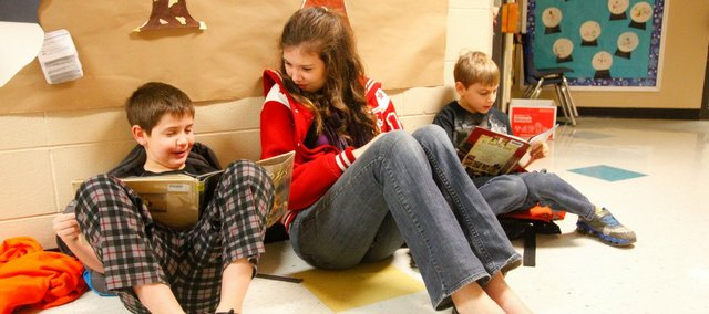 Tonganoxie Elementary School third-grader Austin McCowan, left, reads with Tonganoxie High School junior Celeste Bartels. Damon Paquette, right, also reads during Early Birds reading Thursday morning at TES. Bartels started the Early Birds program this year. Fellow THS students also assist with the before-school program.