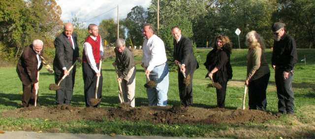 Mayor Jason Ward (in red) turns dirt along with members of the Tonganoxie City Council at the ground breaking ceremony Friday for the Chieftain Trail.