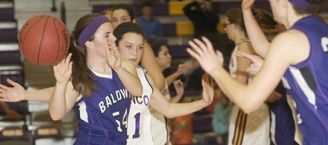 Baldwin senior Hailey Cope makes a no-look pass in the second half of the Bulldogs' game Friday at Spring Hill. Baldwin came back from an early 10-point deficit only to lose, 52-50, in the final seconds.