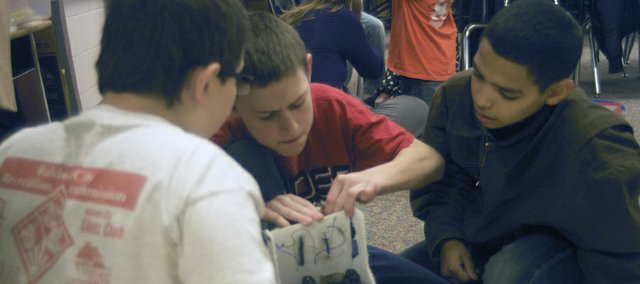 From left, fifth-graders Sterling Judy, Caden Wintermantel and Donavyn Phillips work on a battery powered car they will enter into Thursday's Baldwin school districts elementary school science fair. The three-member team is attempting to build a model car faster than those that can be bought off the shelf.
