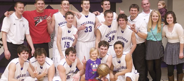 The Baldwin boys basketball team, coaches, managers and a few friends pose with the first-place trophy for the Baldwin Invitational Tournament after the Bulldogs won the title game, 61-57.