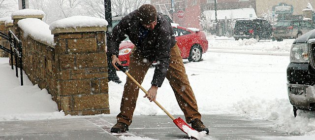 Brian Sheldon clears a downtown Baldwin City sidewalk during a snowstorm several years ago. The American Heart Association says people should be mindful that the activity could cause heart problems and offers tips of avoid heart attacks.