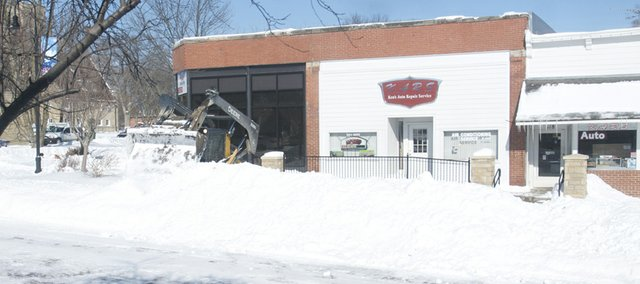 A city employee makes an impressively high wall late Wednesday in the middle of High Street from snow plows pushed to the curb. Digging out from Tuesday's storm that dumped up to 10 inches on the community was an activity that occupied most city residents Wednesday.