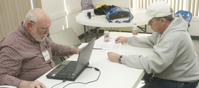 Robert Quinn of Baldwin City looks over a tax statement while AARP Foundation Tax Aide volunteer Gordon Montney prepares in tax return Tuesday at the Lumberyard Arts Center. The free service will offer service by appointment from 12:30 to 4 p.m. Tuesday at the Lumberyard through April 15.