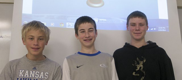 From left, Jake Grossner, Jacob Bailey and Britten Coates stand under a CAD drawing of a shape table Grossner drew as part of the national Christopher Columbus Awards contest they entered on a team that includes Joss Bathke (not pictured). The four seventh-graders proposed a mobile lab equipped with tools an occupational therapist could use at rural Kansas schools.