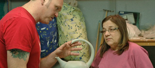Trent Freeman, left, discusses how to appropriatley level the bottom of a teapot with student Mary Thompson.