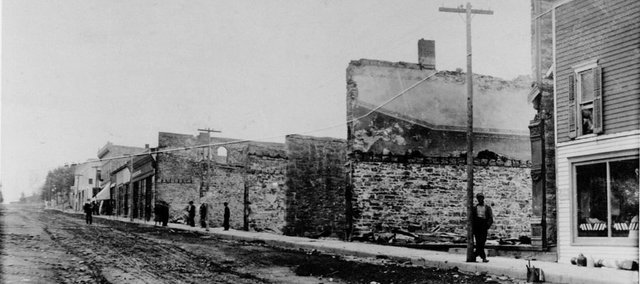 Citizens wander Oak Street, looking at the burned out building shells after the October 1908 fire that destroyed up to 22 downtown businesses in the 100 block of the street. From the Urbin Ruddell collection.
