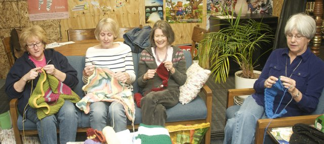 Barbara Mathews, Gloria Hinshaw, Helen Graettinger and Carol Anderson knit items for the Christian charity World Vision during their weekly needlework circle Monday at the Baldwin City Public Library. The group invites other to join them for the weekly knitting and socializing gathering.