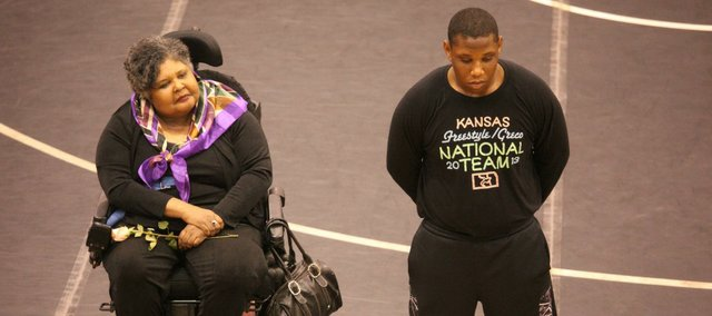 Johnathan Carter, right, and his mother Lorna Simms-Carter listen as Johnathan is recognized at senior night on Jan. 30. It would be the final time Lorna would see Johnathan wrestle in high school as she was unable to attend Class 4A state in Salina like she had hoped.