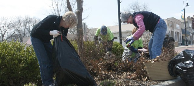 Baldwin City Garden Connection's members, from left, Helen Graettinger, Donna Masoner, Jane Akob and Carol Anderson work to prepare for the season the planter in front of the Baldwin City Public Library. The members take care of the downtown flower beds and hanging baskets as well as the bed near the swimming pool throughout the growing season.