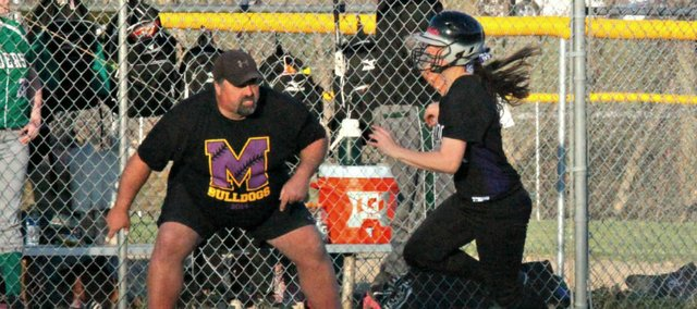 McLouth coach Ballard Patterson waves senior Konner Patterson home in the Bulldogs' second game against Leavenworth-Immaculata on Thursday. Konner Patterson went a combined 5-of-6 in the two-game sweep.
