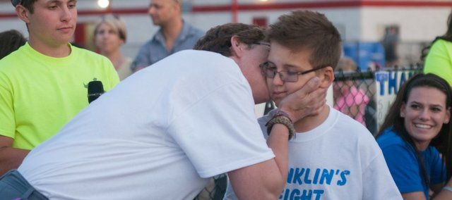 Franklin Eason gets a kiss from his mother, Linda Eason, during Friday's Light Up the Night for Franklin's Fight at Beatty Field.