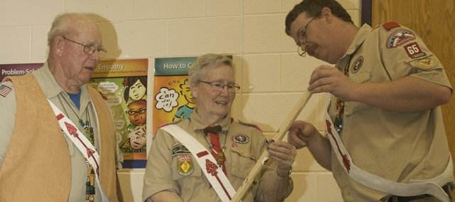 Baldwin City Troop 65 Scout Master Jeff Lundry presents Betty Lawrenz with a staff Sunday signed by the troop's scouts in honor of her 50-year association with scouting. Also in the photo is the honoree's husband, Robert Lawrenz.