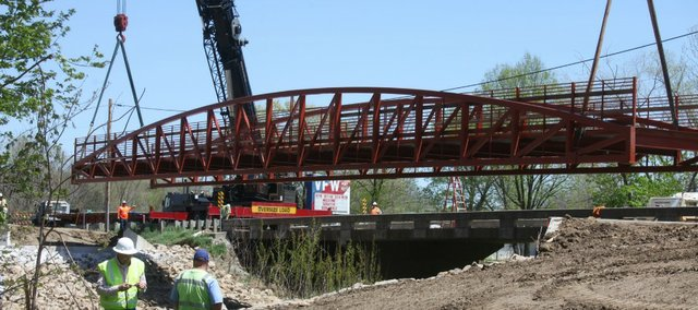 Crews move a walking bridge Friday to its new home along Leavenworth County Road 5. The bridge connects the current Chieftain Trail to its next phase, which connects to the northeast portion of Tonganoxie.