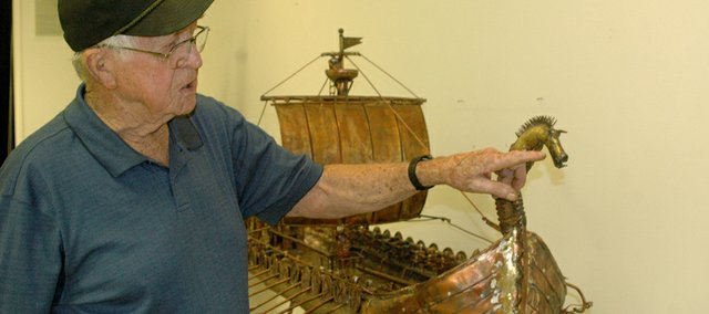 Harold Leible gestures to the dragon head on his copper replica of a Viking boat, one of about 20 of his welded creations on display at the Wyandotte County Historical Museum.