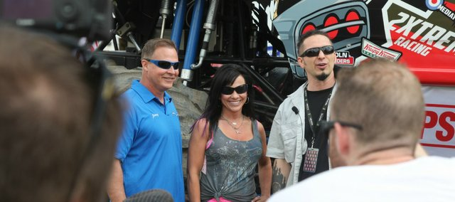 From left, Jimmy Creten, Dawn Creten and Zoltan Bathory smile for several cameras Saturday before Bathory, guitarist for Five Finger Death Punch, got in a monster truck for the first time.