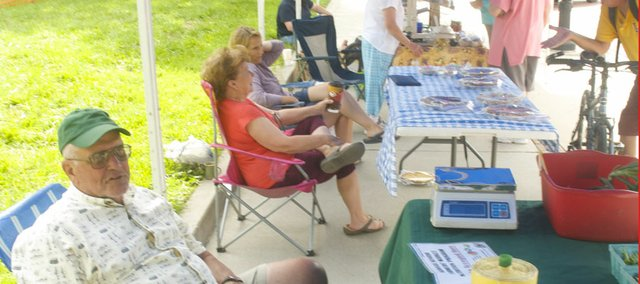 From left, Jim Johnson of Lone Star Farms, Charlene Potter, Charlene Hannon and Linda Hoffman wait or talk to customers during Saturday's Baldwin City Farmers' Market west of the Post Office. The vendors said it was a slow day but that things would pick up when fresh summer produce started showing up during Saturdays next month.