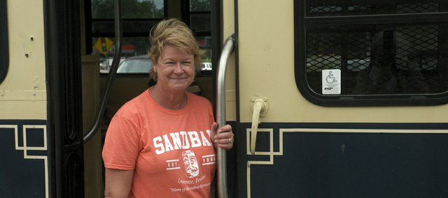 Peach Madl stands at the passenger entry door to the trolley bus the Baldwin City Tourism Council and Baldwin City Economic Development Commission recently purchased. Madl serves as tour guide of the historical tours offered Saturday on the bus.