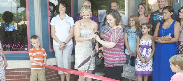 Michelle Beas (left with scissors) and Tisha Voights formally open their In Focus photo studio at the corner of Eighth and High streets downtown Friday during a Baldwin City Chamber of Commerce ribbon cutting.