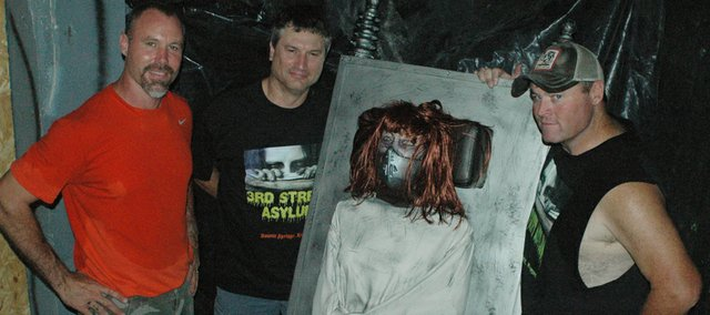 Third Street Asylum owners (from left) brothers Jerry and Steve Hoffine and Mike Clouse (posing with Crazy Christa, the newest animatronic member of the asylum) have created a new Tiblow Days tradition with their haunted house sneak peek event.