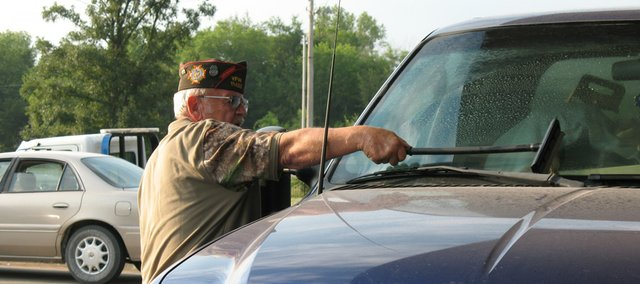 Basehor VFW Post 11499 member Fred Box washes a windshield Friday at the Basehor Casey's General Store during the VFW's fundraiser for the Muscular Dystrophy Association.