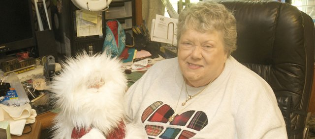 Olive Buehler takes a minute at her work place in her Wellsville home to show off one of the Santa Claus figurines she will bring to the Maple Leaf Festival.