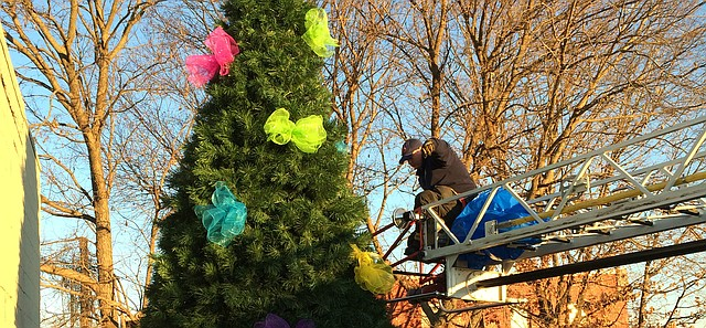 The Tonganoxie City Fire Department decorates the city's Christmas tree Wednesday in the pocket park where the police department previously stood. The tree officially will be lit up for the first time Saturday as part of the the Mayor's Christmas Tree ceremony.