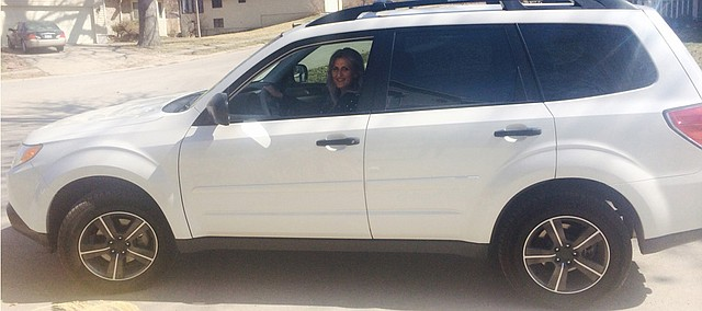 Suzanne Lee Hern smiles behind the wheel of her new car, purchased with the help of donations from a March 6 fundraiser. Recuperating from a life-threatening car accident in December, Hern said the safety rating was a top priority for her new car.