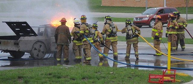 Firefighters with the Baldwin City Fire Department and the Palmyra and Willow Springs departments train on props  Wednesday from a Kansas University Fire and Rescue Training Institute trailer. Underneath the flames is a prop garbage dumpster. The car would be the next training prop.