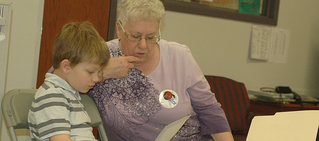 "Nancy McGowan listens Tuesday as Landon Bragg, second grader at Bonner Springs Elementary, reads the poem ""One Inch Tall."" McGowan and 11 other members of the Bonner Springs Senior Center have been visiting the school for the past two months to help tutor the students as they hone their reading skills."