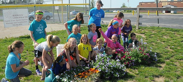 Young students in the Girls on the Run program pose last week with the flowers they planted as this spring's community service project. The program promotes healthy lifestyles and self-esteem through running and will conclude with a 5K this month in Overland Park.