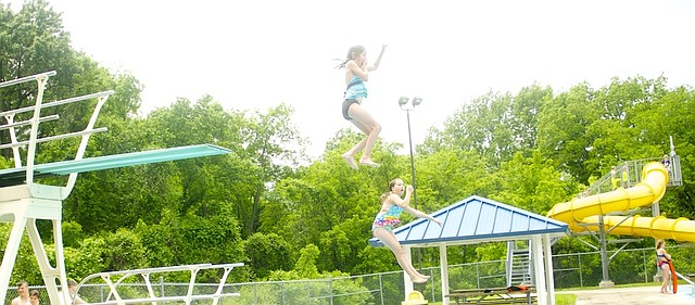 Sisters Alison Bayless, 7, and Haylee Bayless, 13, show off their synchronized diving skills as they jump into the Baldwin City Municipal Pool on its opening day Monday. The pool is open from 1 to 7 p.m. daily this week, but the season really gets going Monday with the start of morning adult lap swims and swimming lessons.