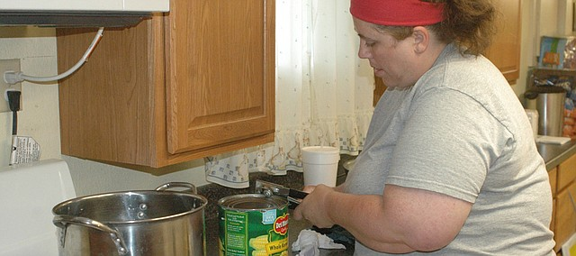 Erin Mahan opens a can of corn as she begins to prepare food Monday for the free weeknight dinners now offered at Olivet Church of God in Christ, 201 Springdale Ave.