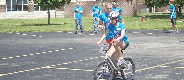 ICan Shine camp floor leader Kenan Brod runs along side of Faith Wallis at a Friday session of the ICan Shine bicycle camp on a Baldwin High School parking lot. With the help of 88 volunteers, 27 individuals with physical and/or developmental disabilities learned to bike at the five-day camp.