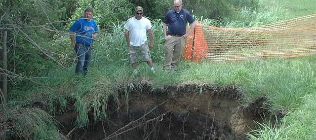 Basehor city officials inspect the sink hole on the south side of Parallel Road, which is about 10 feet deep and extends beneath the road, causing another hole to form on the north side of the road.