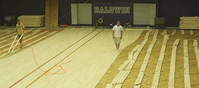 Workers laid strips of new flooring Tuesday on the Baldwin Junior High School Gymnasium. The work continued into the school year when the contractor was delayed in getting to gym and then found problems with sub-floor once the old floor was removed.