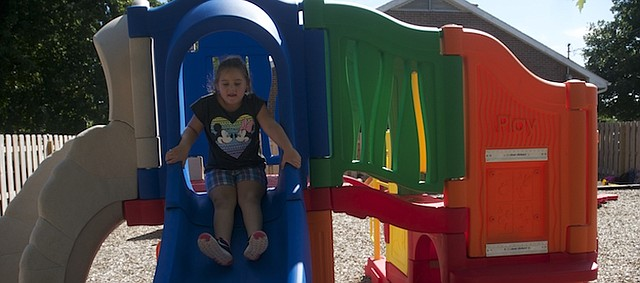 Karley Moutney readies to make use of the slide in the Rainbow Experience Daycare's new playground, which was installed last spring. With the playground in place, Rainbow is offering an all-day option for the first time.