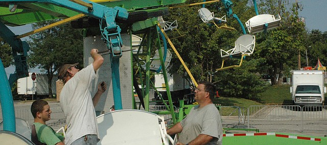 Jones and Company carnival employees install a seat Wednesday on the Cobra, a popular Tiblow Days ride. The carnival opens today at 3 p.m.