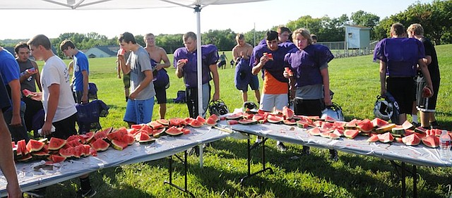 Baldwin High School football team members cool down Thursday with watermelon the Knights of Columbus provided at the end of practice. Fans will get a peek at this year's team at the annual purple-white game Friday.