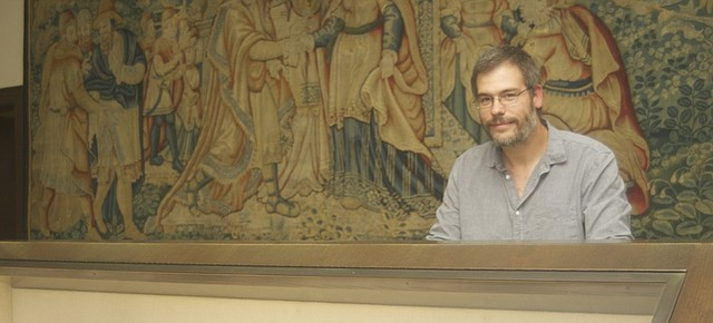Nick Pumphrey leans on a display case with books from this year's exhibit of the Quayle Bible Collection materials. The show, which will run through July 31, 2016, explores multi-faceted biblical story of King David, highlights of which are featured on the tapestry behind Pumphrey.