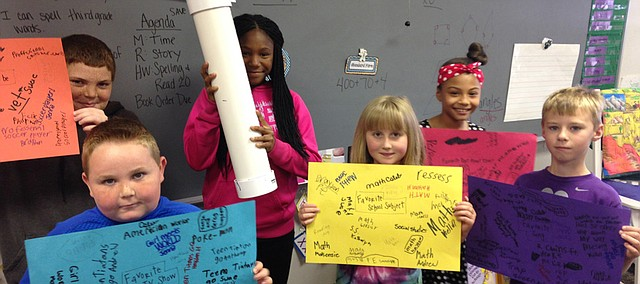 Edwardsville Elementary students hold up the sheets listing the popular television shows, movies, songs and more of today, which will be placed in a time capsule that will be buried in Edwardsville City Park for the city's 100 Year Celebration Sept. 19. From left are Marquel Feullingdavis, fifth grader; Jacob Robinson, third grader; Shay Royal, fifth grader (holding the time capsule); and third graders Kara Stewart, Olivia Marshall and Andy Streit.
