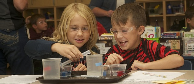 Second-graders Danica Peterson (left) and Braxton Chase are all smiles as the measure out ingredients for making slime during a science lesson Monday in the Baldwin Elementary School Primary Center classroom of Stephanie Ramirez. Greenbush, the Southeast Kansas Educational Service Center, provided the lesson with the first-ever trip of its mobile science lab.