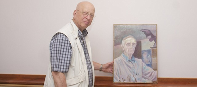 Walt Bailey displays a self-portrait of his late friend and colleague, Tom Russell. It is one of the 27 works he gathered for a show honoring Russell, who died in July at the age of 97. The show opens Friday and will run through Oct. 24.