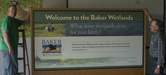 Jon Boyd, manager of the Baker Wetlands, and his father Roger Boyd, Baker director of natural areas, show off one of the display cases with graphic panels that would be on display at the Baker University Wetlands Discover Center. There will be an open house for the new Discovery Center from 9 a.m. to 4 p.m. Saturday and 1 to 4 p.m. Sunday.