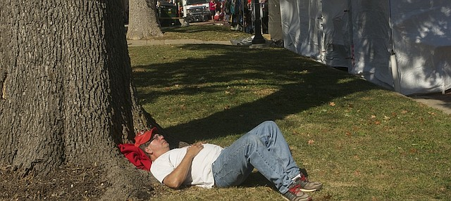 Kyle Fitzgerald of Baldwin City takes a rest Sunday at the Maple Leaf Festival as his wife continues to shop. The festival wrapped up Sunday with beautiful fall weather than helped push estimated attendance to better than 30,000.