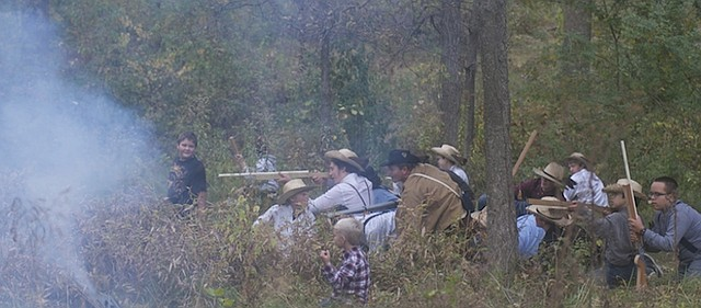 Boy Scouts playing the role of Henry Pate's militia fire on the forces of John Brown in a re-enactment Saturday of the Battle of Black Jack. Eleven local Boy Scout troops and one Cub Scout pack took part in a camporee last weekend at the historic site, which included to re-enactments of the 1856 battle complete with smoke and recorded gunfire.