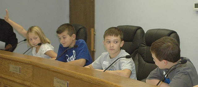 Georgia Moore raises her hand to speak as a council member Wednesday morning during a mock city council meeting with fellow Basehor Intermediate School third graders Christian Locke, Nicholas Hotujac, and Talin Turner, who was playing the mayor.